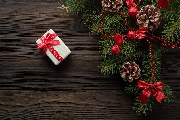 Casella bianca con un fiocco rosso su un tavolo di legno con l'ornamento di natale