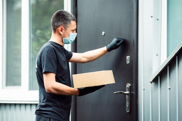 Casella di acquisto consegna a domicilio uomo che indossa guanti e maschera protettiva offrendo pacchetti alla porta