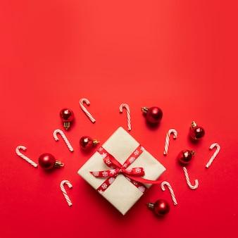 Casella festiva del mestiere di natale con il nastro, le sfere e i dolci rossi su un colore rosso.