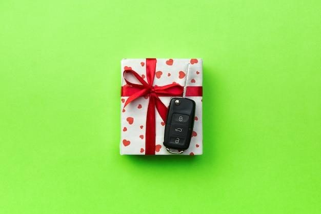 Casella presente con fiocco di nastro rosso, cuore e chiave auto sul verde