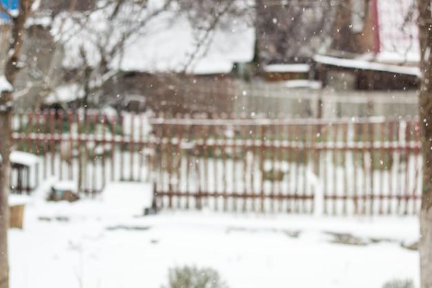 Casette ed alberi vaghi del villaggio di inverno della neve del fondo