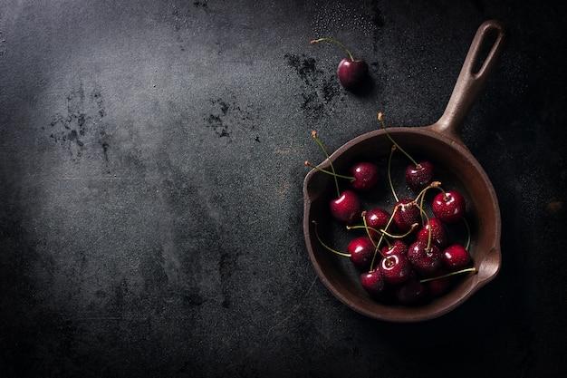 Casseruola con ciliegie su un tavolo di legno nero visto dall'alto