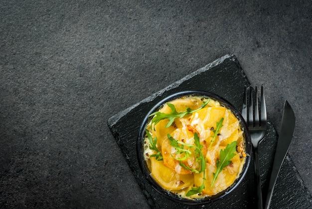 Casseruola. cucina francese. gratin di patate fatto in casa in una ciotola per la cottura