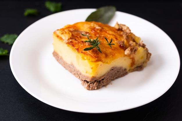 Casseruola del manzo di purè di patate organico casalingo di concetto dell'alimento sul piatto ceramico bianco sulla pietra nera dell'ardesia