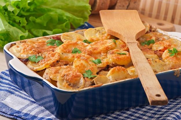 Casseruola di patate con carne e funghi con crosta di formaggio