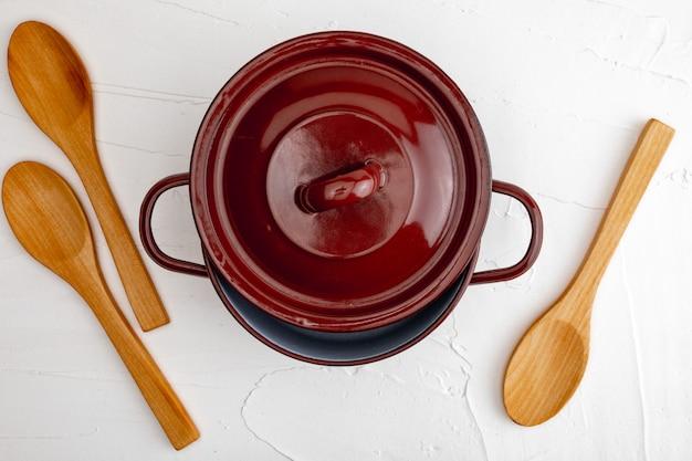 Casseruola e cucchiai di legno. spazio per inserire qui il testo. lettera per i ristoranti. (concetto di cibo di cucchiaio, pentola).