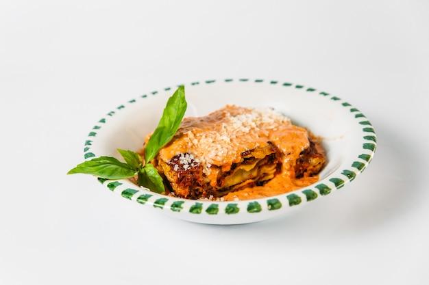 Casseruola italiana delle lasagne al piatto di cucina isolata