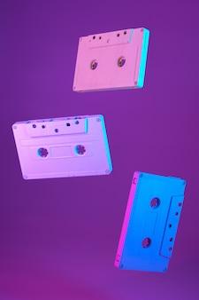 Cassetta a nastro stile vintage sospeso in aria su sfondo viola