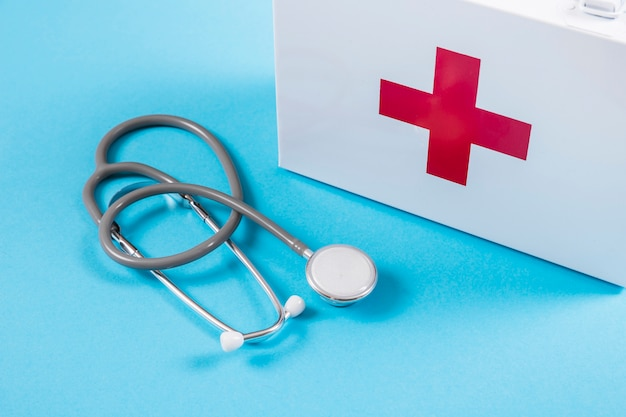 Cassetta di pronto soccorso e stetoscopio bianchi su fondo blu