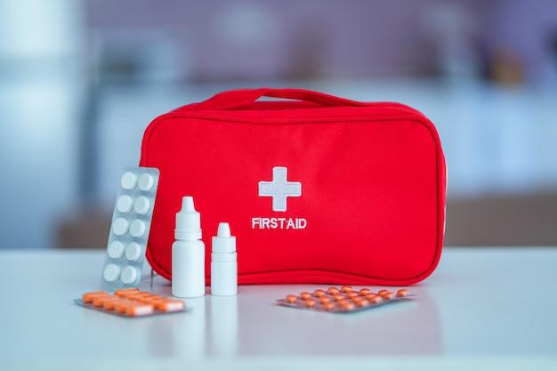 Cassetta di pronto soccorso medica con medicina e pillole sulla tavola a casa