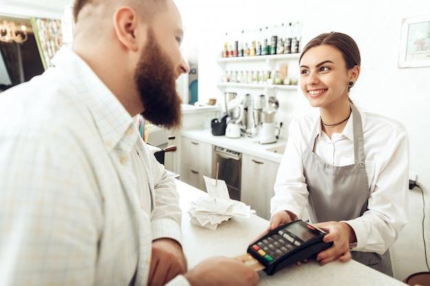 Cassiere allegro utilizzando il dispositivo digitale per il pagamento