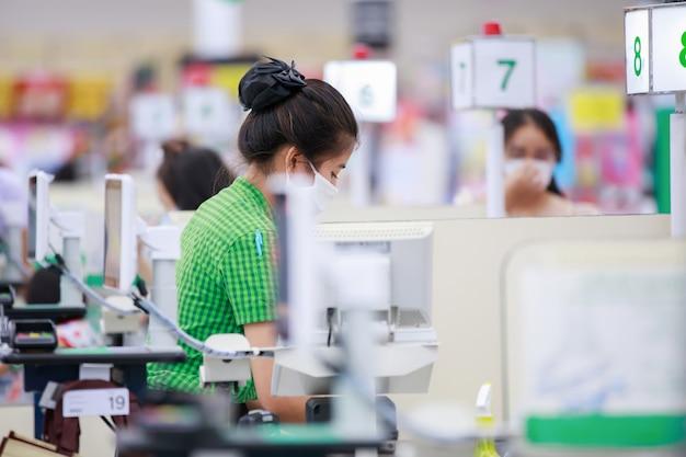 Cassiere in maschera protettiva medica che lavora al supermercato