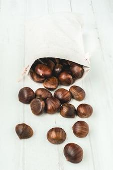 Castagne crude in un sacco gettate su uno sfondo bianco.
