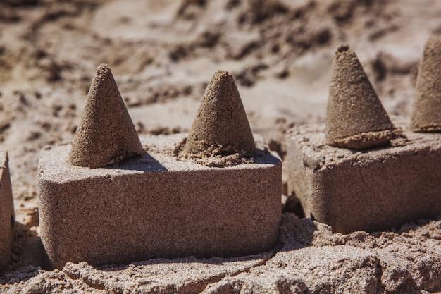 Castello di sabbia in piedi sulla spiaggia. concetto di vacanze di viaggio.