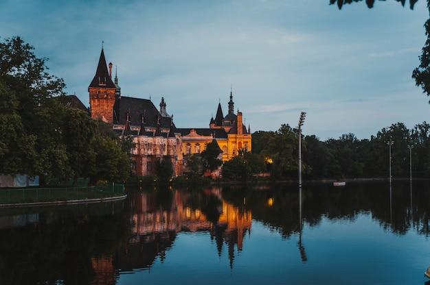 Castello di vajdahunyad a budapest al tramonto con la riflessione dell'acqua.