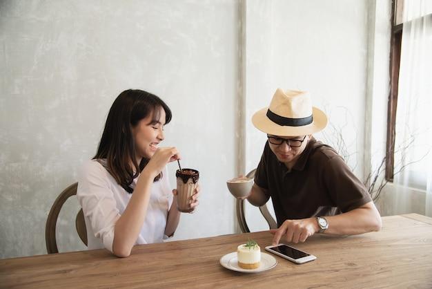 Casual uomo e donna parlando felicemente mentre bere un caffè e guardando il telefono cellulare