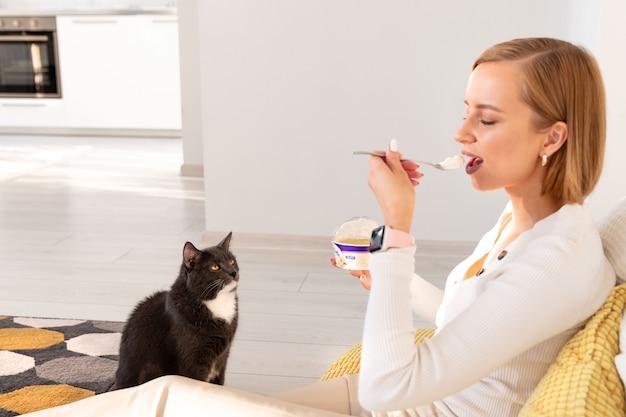 Cat chiede cibo dal suo padrone mangiando yogurt