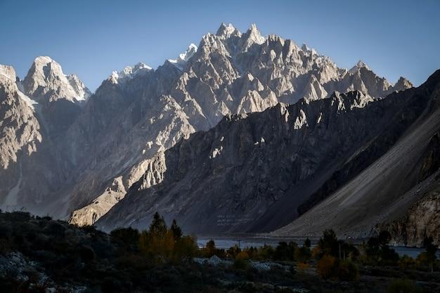 Catena montuosa del massiccio illuminata luce solare con un chiaro cielo blu