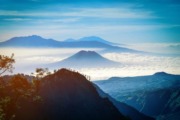 Catena montuosa nella nebbia con la luce del sole.