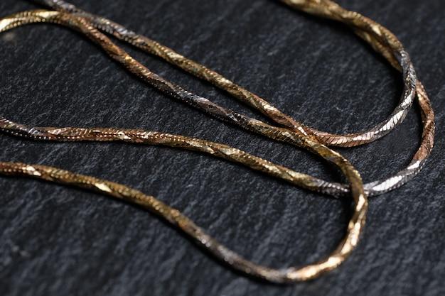 Catena sottile in oro su pietra nera.