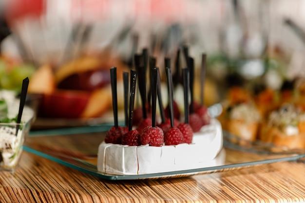 Catering. cibo per feste, feste aziendali, conferenze, forum, banchetti. diversi tipi di formaggio costoso con lamponi. messa a fuoco selettiva