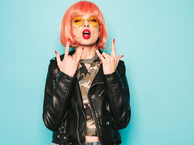 Cattiva ragazza dei giovani bei pantaloni a vita bassa in giacca di pelle nera e orecchini nel naso donna spensierata sexy che posa nello studio in parrucca rosa vicino alla parete blu modello sicuro in occhiali da sole mostra il segno di rock-and-roll