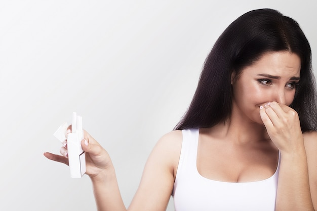 Cattivo odore di sigarette. la giovane donna tiene le sigarette in mano. chiude le mani con il viso. contro il fumo il concetto di salute. su uno sfondo grigio.