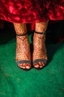 Cattura indiana del primo piano della sposa delle scarpe di ricevimento nuziale