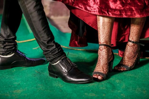 Cattura indiana del primo piano delle coppie delle scarpe di ricevimento nuziale