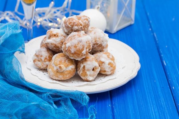 Cavacas portoghesi dei dolci sul piatto bianco su fondo di legno