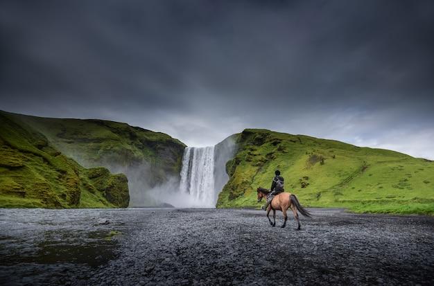 Cavaliere del cavallo vicino alla cascata di skogafoss in islanda in estate.