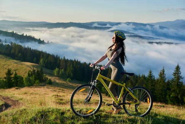 Cavaliere femminile in piedi con la bicicletta in montagna