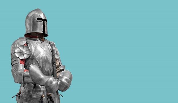 Cavaliere medievale in armatura di metallo lucido su sfondo blu.