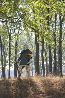 Cavaliere medievale in armatura nei boschi
