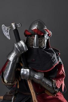 Cavaliere medievale su grigio. ritratto di brutale guerriero faccia sporca con cotta di maglia armature rosse e nere e ascia da battaglia