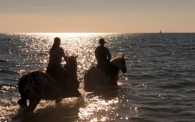 Cavalieri a cavallo nel mare