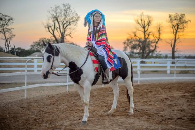 Cavallo da equitazione asiatico sveglio della ragazza al tramonto.