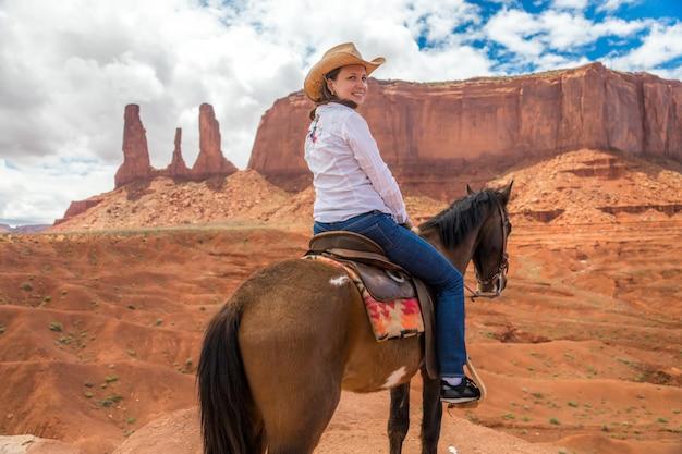 Cavallo da equitazione del cowgirl nel parco tribale navajo della valle del monumento negli sua