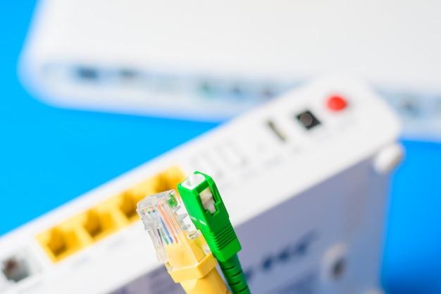 Cavi a fibre ottiche e di rete con router wireless internet su blu