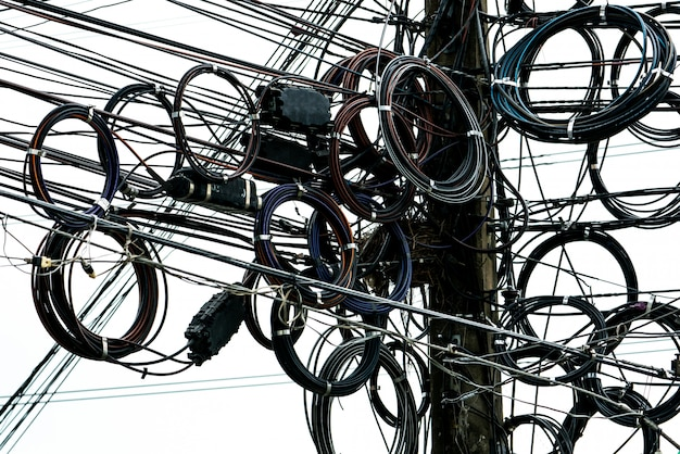 Cavi elettrici aggrovigliati sul palo elettrico urbano.