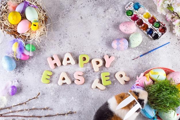 Cavia con le orecchie del coniglietto di pasqua sullo sfondo di pietra di uova colorate