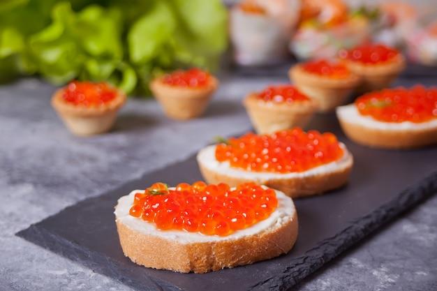 Caviale rosso fresco su pane sulla banda nera. panini con caviale rosso.