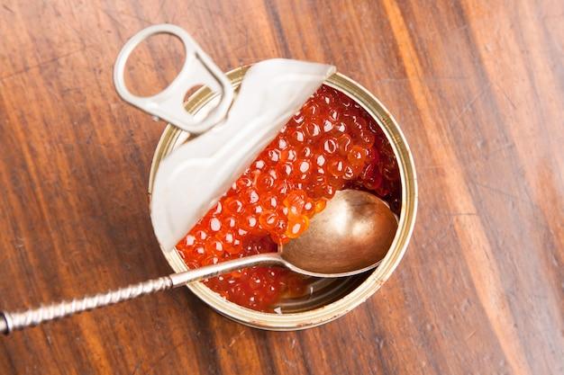 Caviale rosso in banca con il cucchiaio su legno