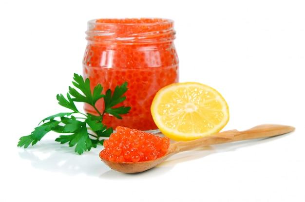 Caviale rosso in un barattolo di vetro con limone e prezzemolo