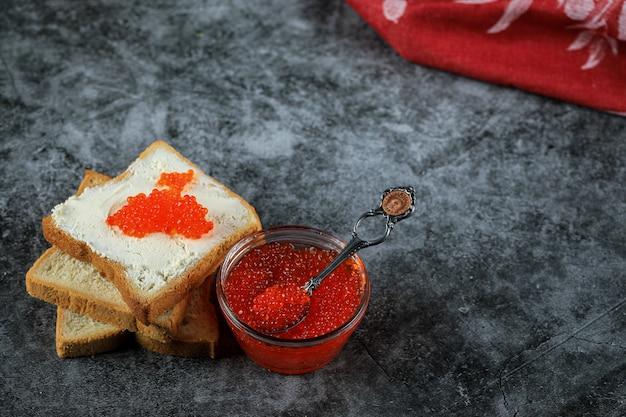 Caviale rosso in un barattolo di vetro e su fette di pane