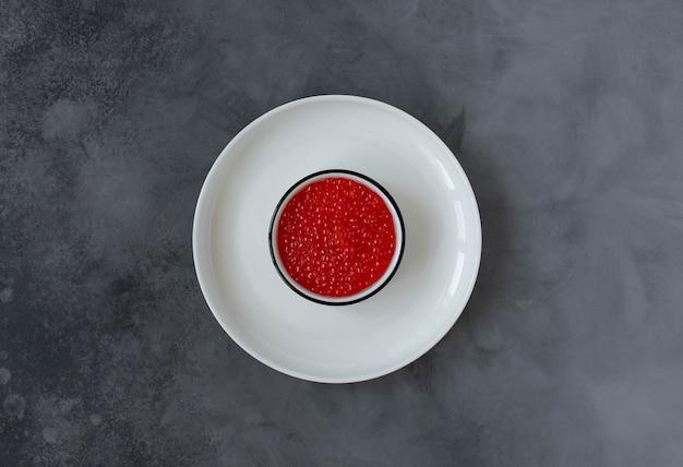 Caviale rosso in un piatto bianco su uno sfondo scuro. vista dall'alto. copia spazio