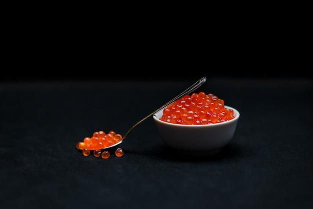 Caviale rosso su sfondo nero. frutti di mare. il concetto di nutrizione sana e naturale. delicatezza russa.