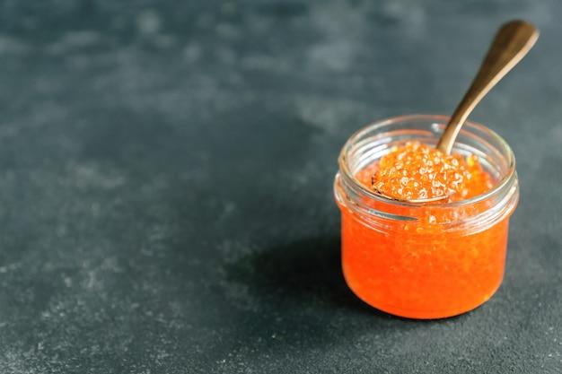Caviale rosso sul luccio di vetro su fondo grigio, frutti di mare. alimentazione sana e dieta. copia spazio per il testo