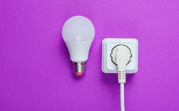 Cavo bianco collegato alla presa di corrente e lampadina a led sul tavolo viola. vista dall'alto