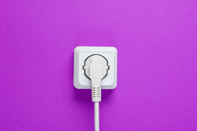 Cavo bianco collegato alla presa di corrente su una parete viola